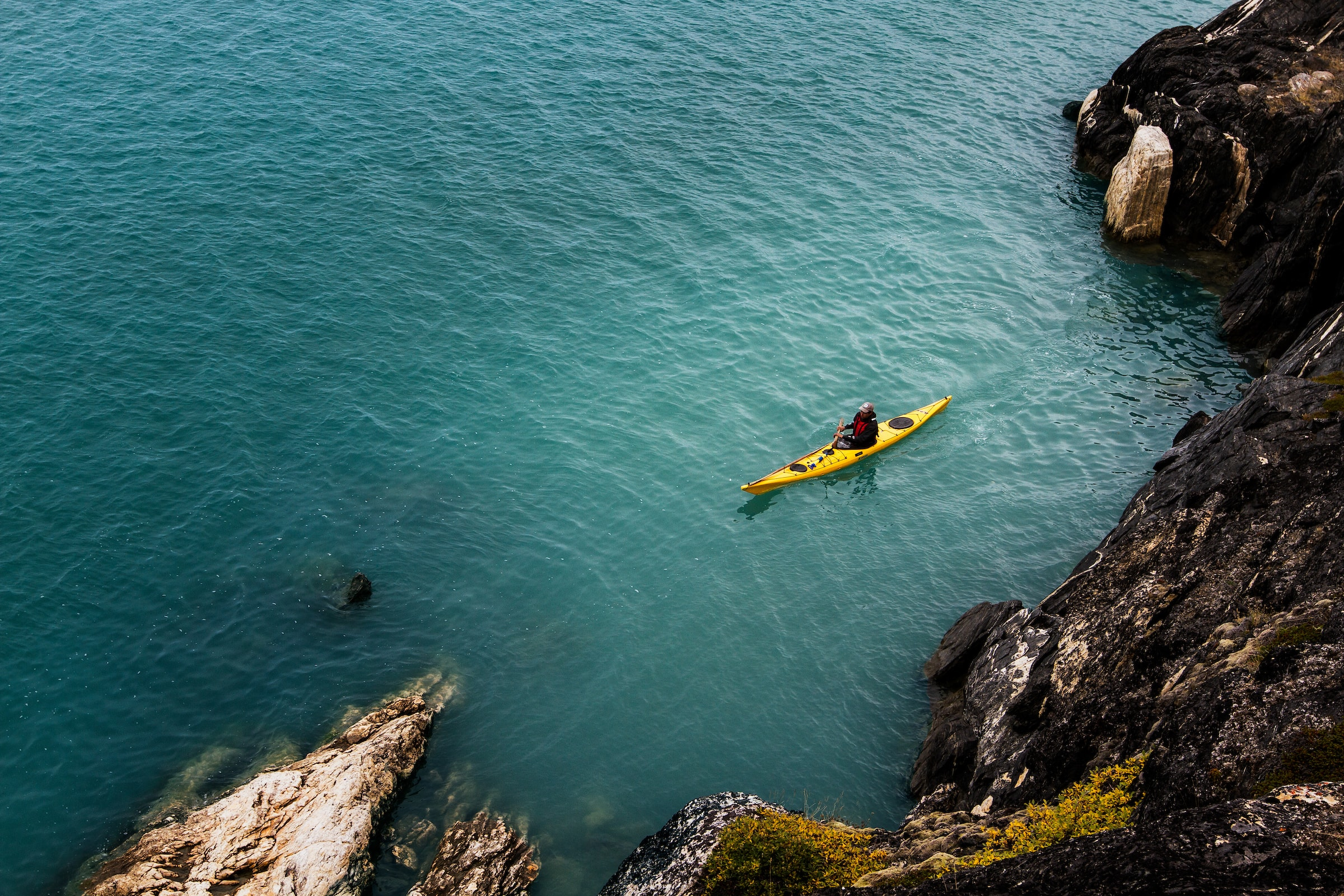 Kayaking along the cliffs of the Kangerlussuaq fjord in Greenland. Photo by Mads Pihl - Visit Greenland