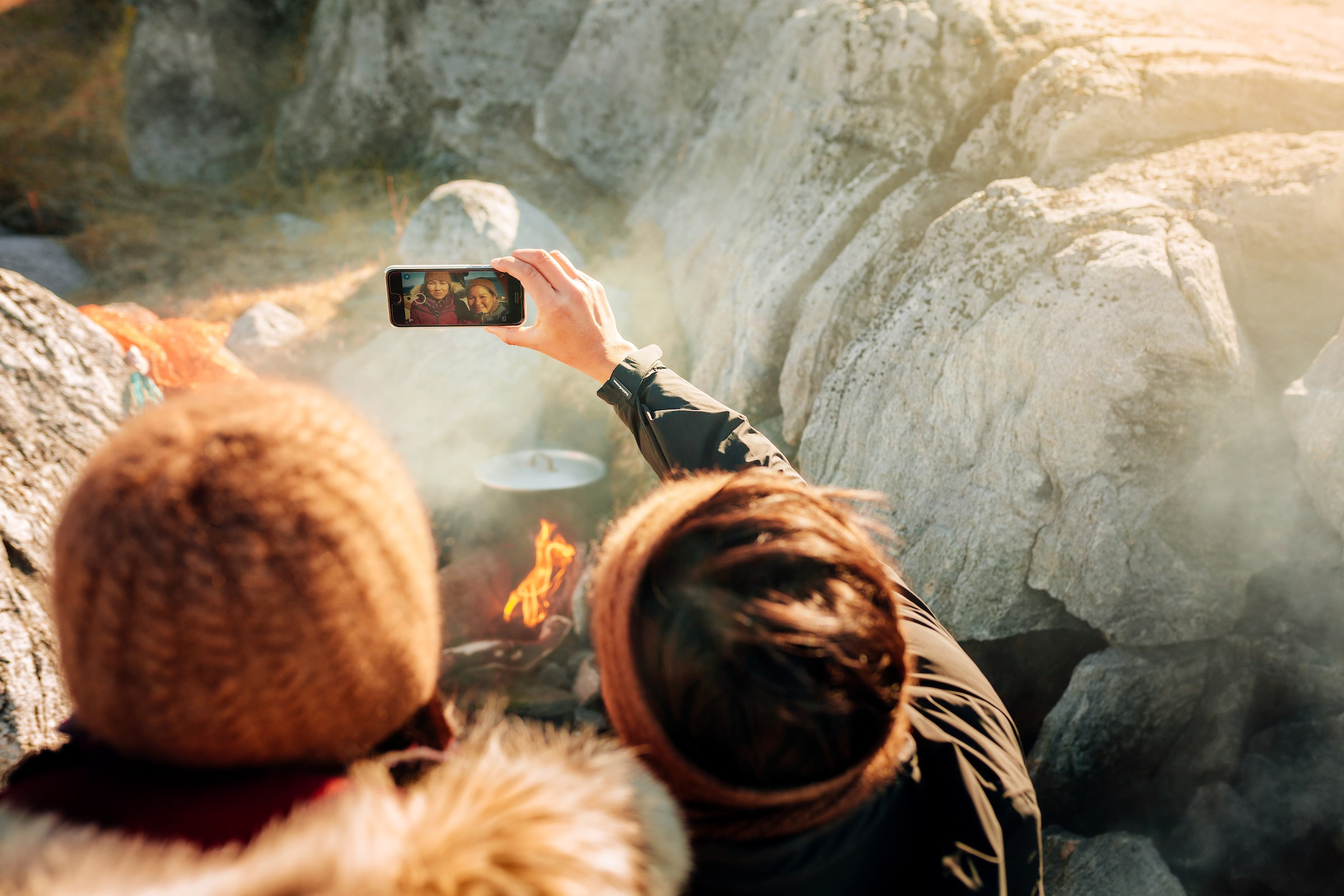 Two women taking a selfie by the fire on the beach in Nuuk in Greenland